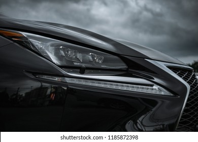 21st September 2018 Chanthaburi Thailand : close up image of car headlight of Lexus nx 300h black color with amazing design against dark storm clouds in background