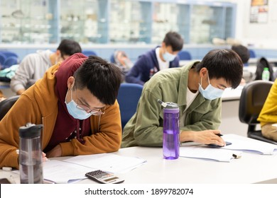 22 01 2021 male and female students doing course or paper work in classroom with face mask in university in Hong Kong during Covid-19