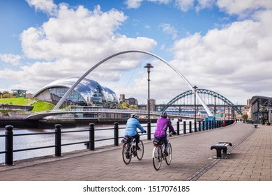 22 April 2016: Newcastle upon Tyne, UK - Cyclists riding along Newcastle Quays, with a view of the Tyne Bridges, including the Millennium Bridge, the Tyne Bridge, and also the Gateshead Sage theatre.