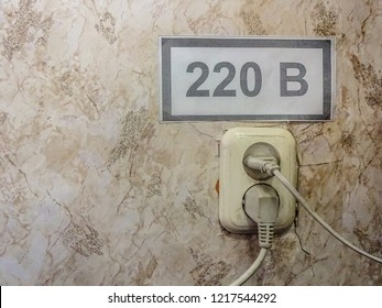 220 Volt outlet in the old room on the background of cracked Wallpaper.