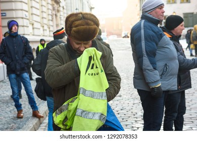 22.01.2019. RIGA, LATVIA.  Man folds yellow vest, during demonstration against new coalition of government of Latvia outside Saeima building (Parliament of Latvia).