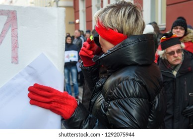 22.01.2019. RIGA, LATVIA.  Woman with red gloves drinking hot tea of thermos, during demonstration against new coalition of government of Latvia outside Saeima building (Parliament of Latvia).