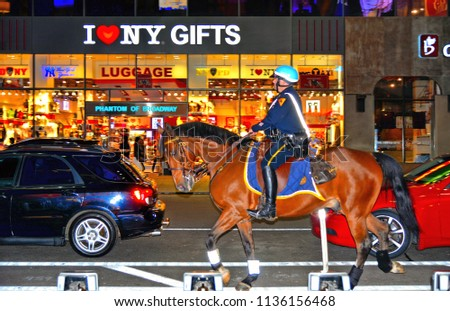 22.05.2016. NYPD police officer on horse back in Times Square New York City with gifts store window in background, Manhattan