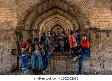 22/05/2019 Isfahan, Iran, people sit and rest in the arches under the Khaju Bridge, they chill in shadow of Khaju Bridge through Zayandeh river