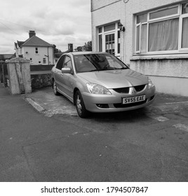 22nd July  2020- An old  Mitsubishi Lancer Elegance, four door saloon car, parked on the road in Whitland, Carmarthenshire, Wales, UK.