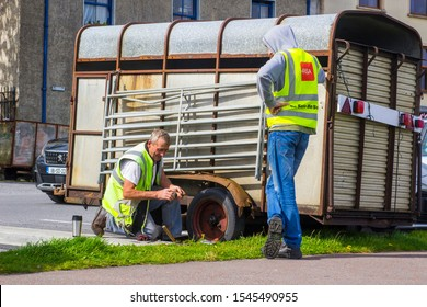 23 August 2019 Men in hi visibilty jackets changing a wheel on a horsebox by the roadside in Mullaghmore village in County Sligo Ireland