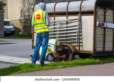 23 August 2019 Men in hi visibilty jackets changing a wheel on a horsebox bythe roadside in Mullaghmore County Sligo Ireland