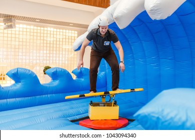 23 FEBRUARY 2018, ULTRA MALL, UFA, RUSSIA: the man participates in the contest trying to balance for a while on for surfing sport simulator