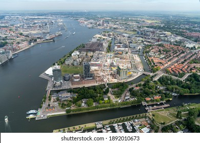 23 July 2020, Amsterdam, Holland. Aerial view of Amsterdam Noord with yacht harbour at lock Willemsluis, river IJ, Adam Lookout, skyscraper Overhoek Woontoren, construction pit and residential area.