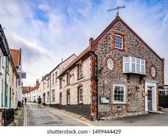 23 June 2019: Blakeney, Norfolk, UK - High Street, Blakeney, with traditional style flint buildings.