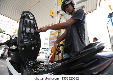 23 MARCH 2019. Petrol station worker fill in a petrol on customer vehicle at petrol station in Johor