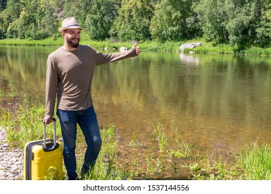 23 year bearded guy with a suitcase stands on the banks of the river. catches transport thumbs up. Space for your text. Concept of travel, journey, holidays, vacation.