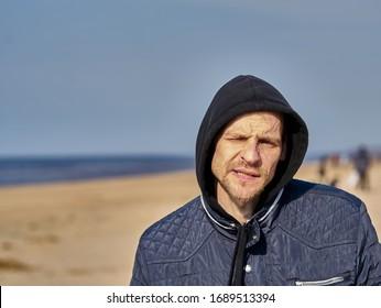 23-03-2020 Riga, Latvia. Portrait of a man in a hood at sea.