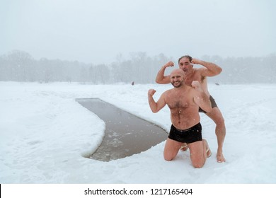 2/3/2018 Russia, Moscow. Two men - walruses do improving swimming in the winter in an ice-hole in the park pose in a pose of body builders at an ice-hole
