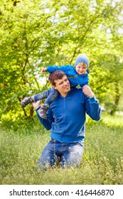 2-3-year-old cute boy dressed in a blue jacket and jeans having fun with his father on the green grass in the park. Spring warm day. Around the beautiful nature. Trees and lush green grass.