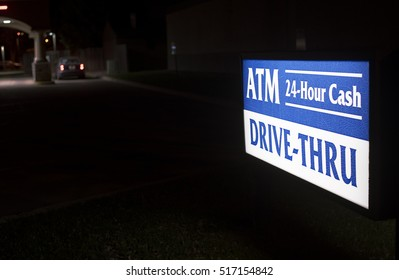 24 hour ATM drive thru illuminated sign, with car at bank in background during night.