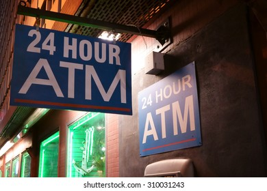 24 Hour ATM sign on side of store on a dark alley.