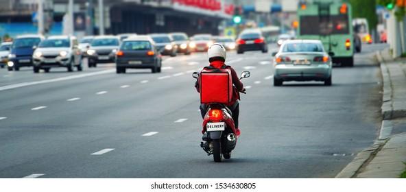 カフェやレストランから24時間の配達サービス。持ち帰り、赤い等温バックパックを持つスクーターに乗った宅配の少年が速く走る。夕方の交通渋滞を避けるためにバイクで食べ物を運ぶ宅配便