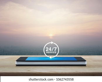 24 hours service icon on modern smart phone screen on wooden table over city tower at sunset, vintage style, Full time service concept