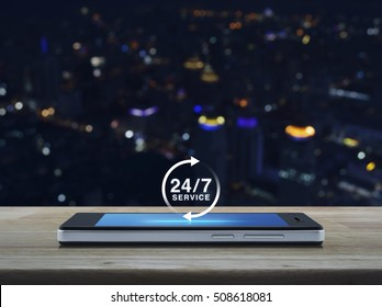 24 hours service icon on modern smart phone screen on wooden table over city tower background, Full time service concept