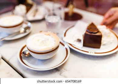 24 MARCH 2017, VIENNA, AUSTRIA: The original authentic Viennese Sacher Torte cake served with whipped cream and cup of coffee at Sacher Hotel Cafe