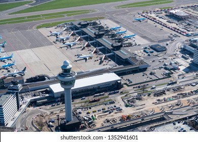24 March 2019, Amsterdam Holland. Aerial view of control tower at Schiphol Airport. Behind a terminal with jet planes from KLM Royal Dutch Airlines, Lufthansa, Swiss and Vueling.