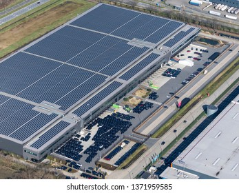 24 March 2019, Tilburg, Holland. Aerial view of Tesla Motors assembly car factory. On the roof many solarpanels and on the parking lot the stock with sold and unsold cars.