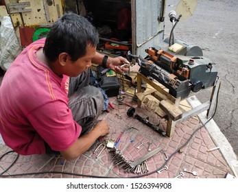 24 September 2019: a key duplicate worker is working with a key duplicate making machine in Sukajadi street Bandung