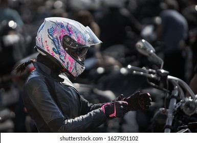 24-04-2019 Riga, Latvia. Biker girl in a leather jacket and helmet on a motorcycle.