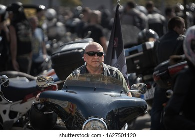 24-04-2019 Riga, Latvia. Serious man in sunglasses sitting on black chopper.