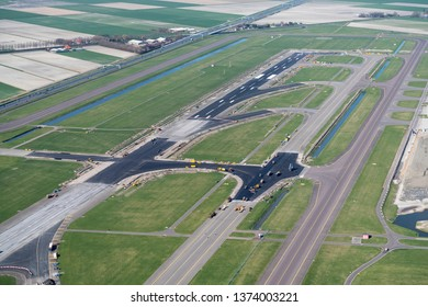 24-3-2019, Amsterdam Holland. Aerial view of renovation of the Zwanenburgbaan, runway 18 and 36 and taxiway at Schiphol International Airport. Heavy machinery like a paver is used on the black asphalt