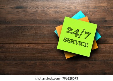 24-7 Service, the phrase is written on multi-colored stickers, on a brown wooden background. Business concept, strategy, plan, planning.