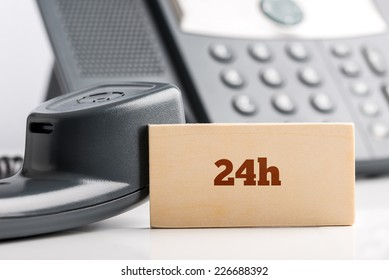 24h business telephone support concept with a small wooden sign saying - 24h - standing alongside a landline telephone instrument with the receiver off the hook in a close up view.