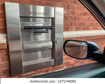The 24-hour drive-thru night depository terminal of a neighborhood bank set on red brick wall and framed through portion of a car.
