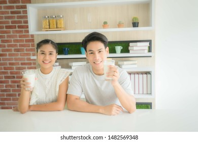 A 24s handsome young asian man and beautiful young asian woman 24 years old smile drinking milk in the morning, A 24s handsome male and 24s beautiful female holding milk in the morning