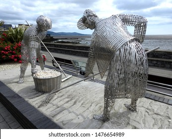 "24th July 2019, Dundalk, Ireland. ""The Cocklepickers""  unveiled on the Blackrock promenade in December 2018 was created by local artist Micheál McKeown made from woven stainless steel."