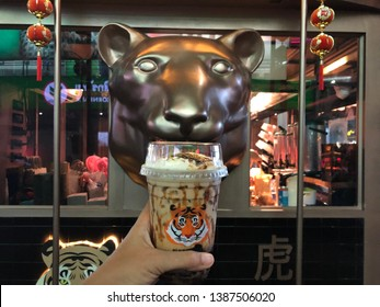 25 April 2019; Siam Square road, Bangkok Thailand: Cup of Fire Tiger Thai Bubble Milk Tea. Fire tiger milk tea is a franchise milk tea drink shop in Thailand.