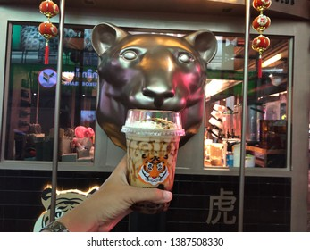 25 April 2019; Siam Square road, Bangkok Thailand: Handed Fire Tiger Bubble Milk Tea Cup. Fire tiger milk tea is a franchise milk tea drink shop in Thailand.