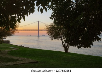 25 April Bridge in Lisbon at sunset seen from a park with trees and grass field