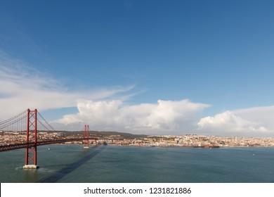 The 25 April bridge (Ponte 25 de Abril) and cityscape. Lisbon, Portugal
