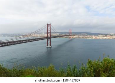 25 de abril bridge (25th of April Bridge), Almada, Portugal. Beautiful red suspension bridge connected to the portuguese capital of Lisbon. Often compared to the Golden Gate Bridge in San Francisco.