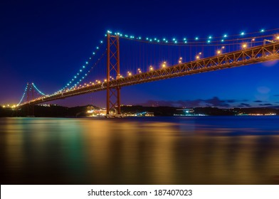 The 25 de Abril bridge over Tagus river and big Christ monument in Lisbon at night, Portugal
