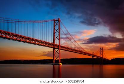 The 25 de April Bridge with Sunset Lights.