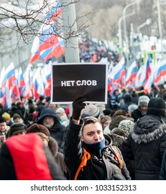 """25 FEBRUARY 2018, MOSCOW, RUSSIA. Young man holding a poster in the crowd with words """"No words"""" in the crowd during the protest in memory of russian politician Boris Nemtsov"""