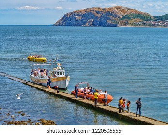 25 July 2018: Llandudno; Conwy; UK - People on the boardwalk or jetty; getting on and off the Sea Jay and a Jet Boat; for rides around the bay, with the Little Orme in the background.