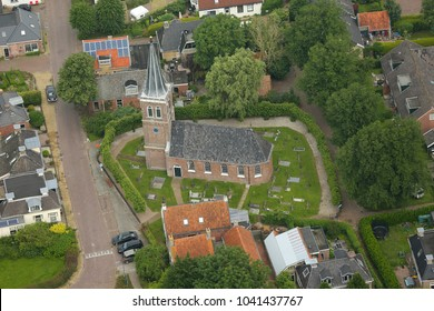 25 June 2016, Baard, Holland. Aerial view of Church in a small town in Friesland. The church has a cemetery  and is surrounded by green trees.