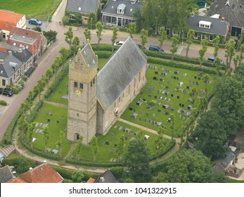 25 June 2016, Jorwert, Holland. Aerial view of Sint Margareta Kerk in Jorwerd, a small town in Friesland. The church has a cemetery  and is surrounded by green trees.