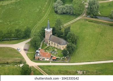 25 June 2016, Leons, Holland. Aerial view of Catharina Kerk in Lions, a small town in Friesland. The church has a cemetery  and is surrounded by green fields.