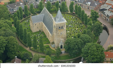 25 June 2016, Oosterend, Holland. Aerial view of Martini Kerk in Easterein, a small town in Friesland. The church has a cemetery  and is surrounded by a circle of green trees.
