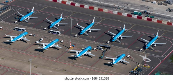 25 March 2020, Amsterdam, Holland. Aerial view of Schiphol International Airport during the Corona crisus. Embraer Airplanes from KLM Cityhopper are grounded.